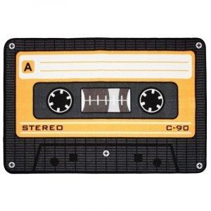 """Nostalgico degli anni 70 e 80? Appassionato di musica della categoria """"si, ma l'analogico è meglio."""" ? Fai capire a tutti l'aria che tira fin dall'ingresso con questo tappetino a forma di musicassetta!"""
